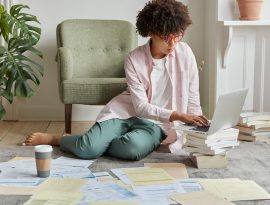 Empreendedorismo: tudo que você precisa para dominar seu fluxo de caixa - Mulher sentada no chão do apartamento organizando as contas