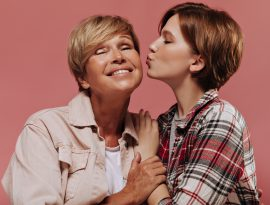 Mãe: símbolo de amor, força e determinação - Young short haired girl in plaid red shirt kissing on cheek her grandmother with blonde hair in beige jacket on pink backdrop.